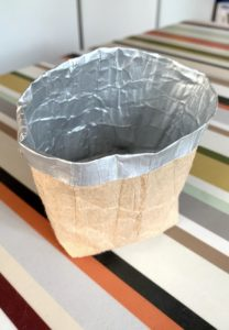 braune Pflanzentasche mit silbernem Rand auf buntem Tisch